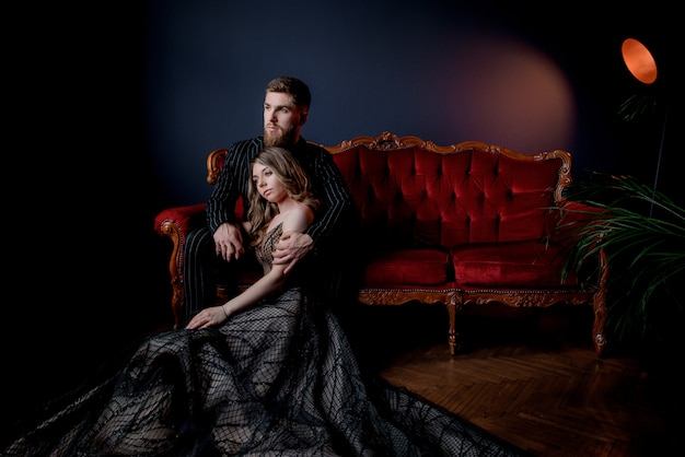 Attractive woman dressed in elegant evening dress and bearded handsome dressed in black suit holding hands together and sitting on the luxury red sofa