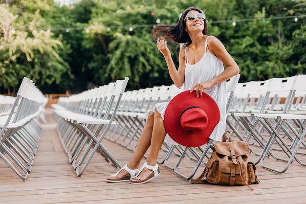 白いドレス、赤い帽子、椅子だけで夏の野外劇場に座っているサングラス、春のストリートスタイルのファッショントレンド、アクセサリー、バックパックと一緒に旅行に身を包んだ魅力的な女性