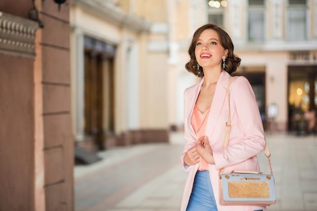 Attraente donna vestita in abito alla moda che cammina per strada di milano per lo shopping