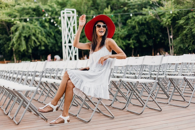 Attractive woman dressed in white dress, red hat, sunglasses sitting in summer open air theatre on chair alone, spring street style fashion trend, accessories, traveling with backpack, waving hand