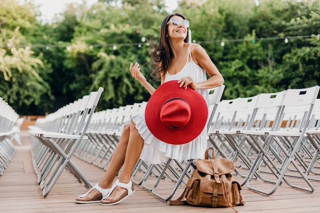 Attractive woman dressed in white dress, red hat, sunglasses sitting in summer open air theatre on chair alone, spring street style fashion trend, accessories, traveling with backpack