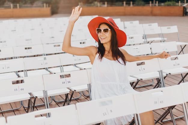 Donna attraente vestita in abito bianco, cappello rosso, occhiali da sole seduti in un teatro all'aperto estivo sulla sedia da solo, tendenza della moda street style di primavera, allontanamento sociale
