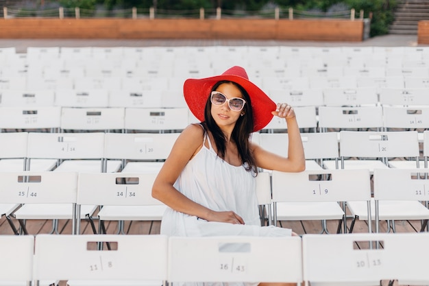Attractive woman dressed in white dress, red hat, sunglasses sitting in summer open air theatre on chair alone, spring street style fashion trend, social distancing