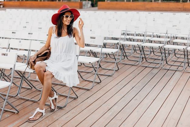 Attractive woman dressed in white dress, red hat, sunglasses sitting in summer open air theatre on chair alone, spring street style fashion trend