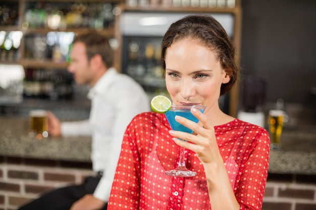 Attractive woman drinking cocktail