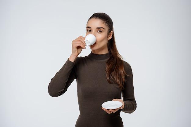 Donna attraente che beve caffè, tenendo la tazza di caffè espresso
