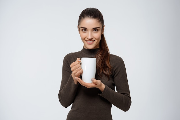 魅力的な女性はお茶を飲んで、カップを保持