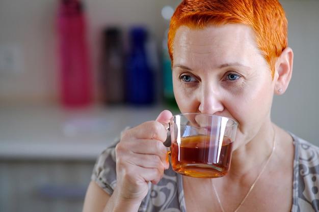 お茶を飲む魅力的な女性。考えてみると、視線は遠くのどこかに向けられています。