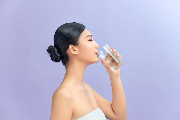Привлекательная женщина питьевой воды на фиолетовом фоне