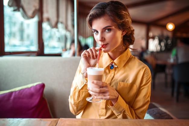 魅力的な女性がレストランでストローからカクテルを飲む