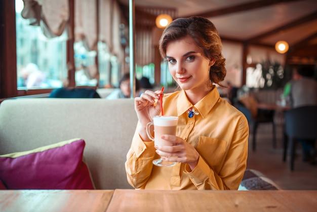 魅力的な女性はストローからカクテルを飲む