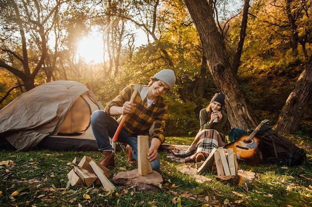 魅力的な女性は、斧で木を切り刻むハンサムな男性のように見えながら、お茶を飲み、丸太に座っています