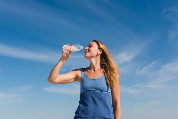 Привлекательная женщина пьет воду из бутылки на открытом воздухе