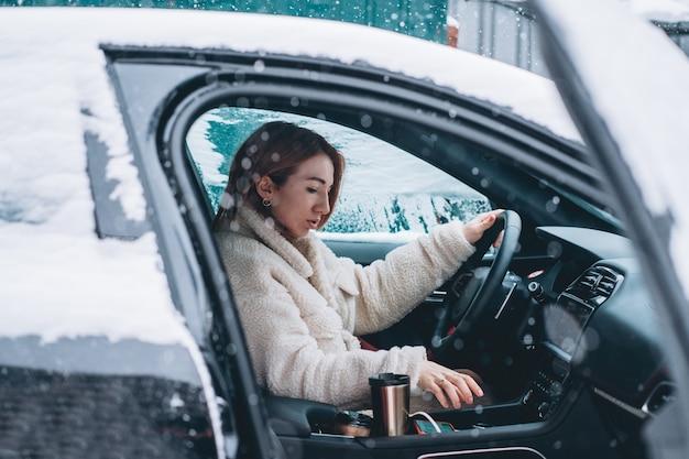 彼女の車のステアリングホイールの後ろに座って魅力的な女性ドライバー