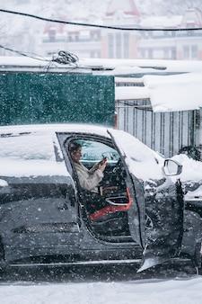 彼女の車のステアリングホイールの後ろに座っている魅力的な女性ドライバー