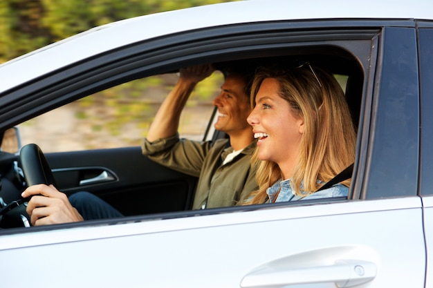 Attractive woman driving car with boyfriend next to her