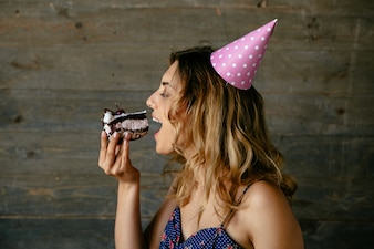 Attractive woman eating a cream chocolate cake, celebrating birthday party