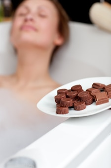 Attractive woman eating chocolate while having a bath