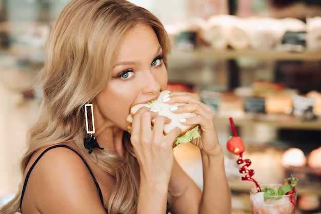 Attractive woman eating delicious sandwich in cafe