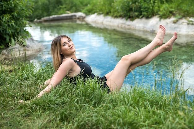 ポンドの近くで自然を楽しむ魅力的な女性、晴れた日