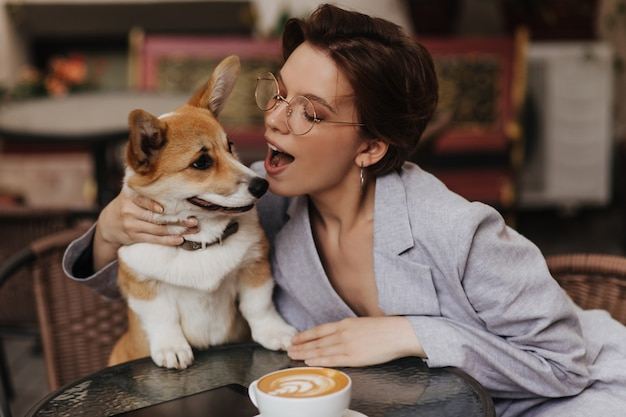 Attractive woman in eyeglasses plays with her dog while resting in street cafe. charming lady in grey jacket kisses corgi