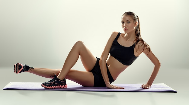 Attractive woman do fitness exercise on a lilac mat
