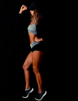 An attractive woman flexing her back on a black background sexy fitness model in a dark studio
