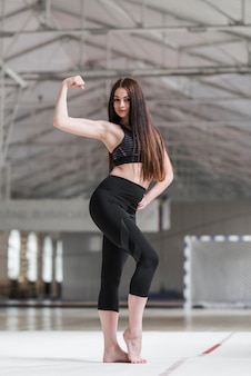 Attractive woman flexing her muscle in dance class
