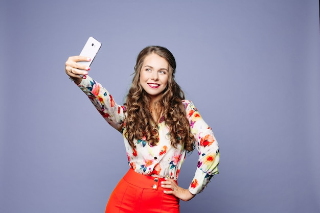 Attractive woman in floral shirt and red shorts taking self-portrait over violet background.