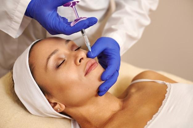 Привлекательная женщина получает инъекцию на губах