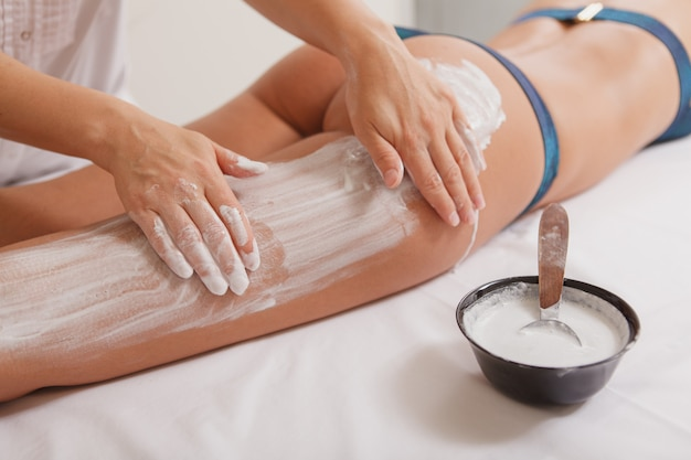 Attractive woman getting body wraps with mask at spa center