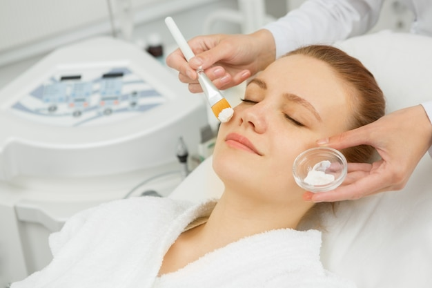 Attractive woman getting facial mask at the spa