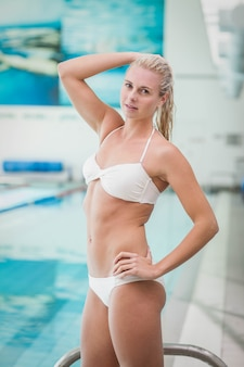 Attractive woman getting in the water at the pool
