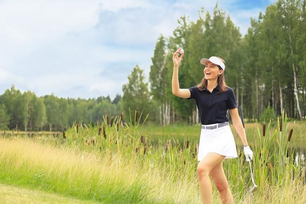 魅力的な女性ゴルフプレーヤーは、ゴルフコースの遠端でボールを見つけます。喜びで顔が輝きます。