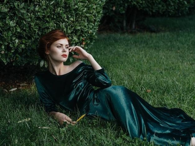Привлекательная женщина зеленое платье роскошный газон очарование зеленого куста элегантный стиль.