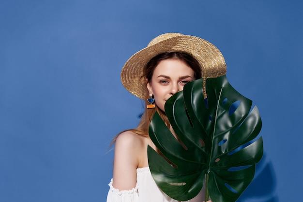 青い背景のポーズをとる魅力的な女性緑のヤシの葉