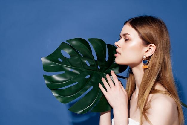 魅力的な女性の緑のヤシの葉のポーズのトリミングされたビュー