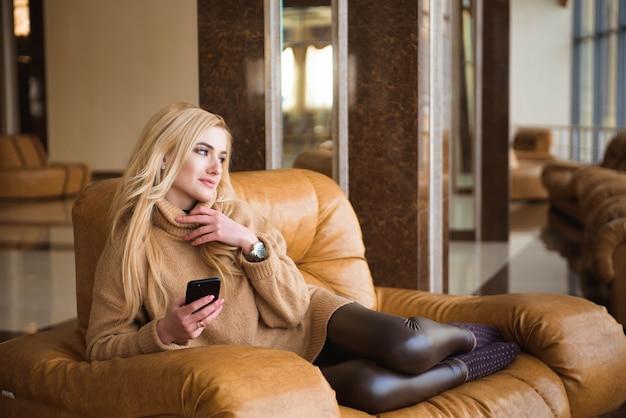 魅力的な女性は彼女の携帯電話を使用してコーヒーブレイクを持っています