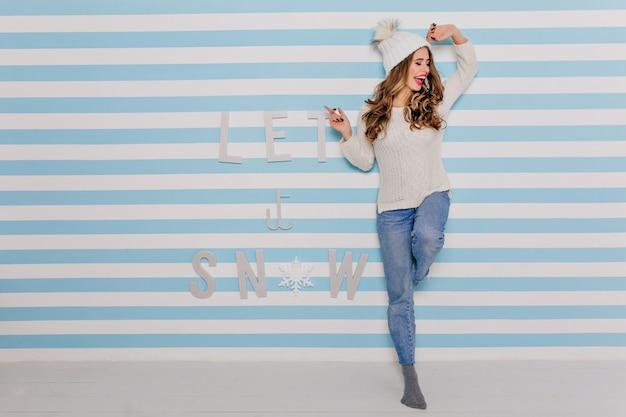 魅力的な女性は楽しんで笑います。白いセーターとワイドジーンズのポーズの女の子