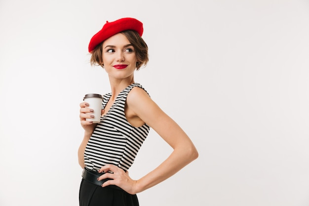 Attractive woman having french style wearing red beret posing on camera with takeaway coffee in paper cup and looking aside, isolated over white wall