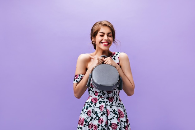 Attractive woman in high spirits poses with handbag. pretty beautiful young girl with rose lips in floral stylish dress posing.