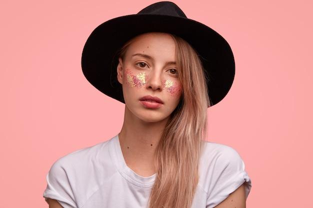 Attraente donna hipster con brillanti scintillii sulle guance, indossa un cappello nero alla moda, maglietta bianca casual, si erge contro il muro rosa
