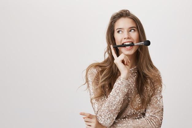 Spazzola attraente della stretta della donna in bocca, distoglie lo sguardo