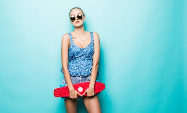 Attraente donna tenere skateboard in cappello e occhiali da sole in posa su sfondo blu.