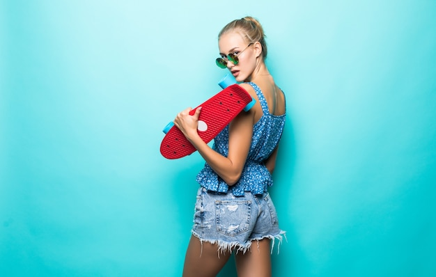 Привлекательная женщина держит скейтборд в шляпе и солнцезащитных очках, позирует на синем фоне.