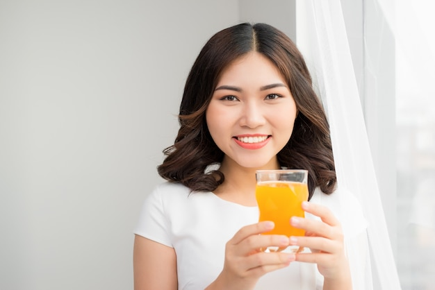 キッチンに立っている間オレンジジュースのガラスを保持している魅力的な女性