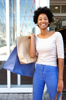 Attractive woman holding bags outside mall