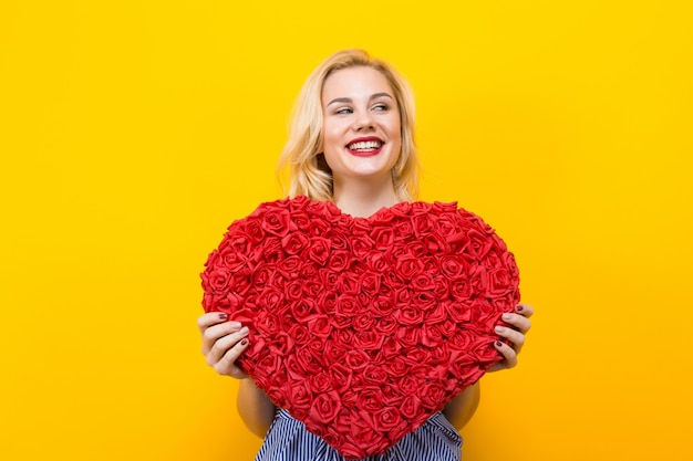 Attractive woman holding big red flower heart