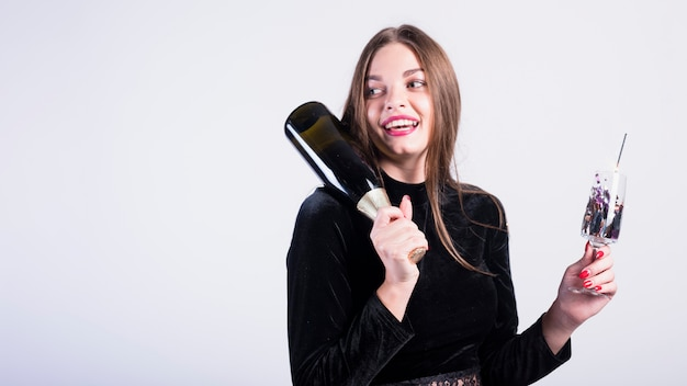 Attractive woman holding bottle of champagne