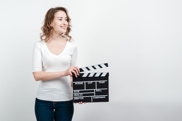 Attractive woman holding a clapboard isolated
